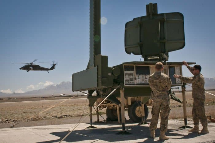 Air traffic control specialists Luke Perkinson and Peter Meppen with 3rd Battalion, 82nd Combat Aviation Brigade, Task Force Corsair, check out the sensor pallet for the FOB Shank air field as a UH 60 Black Hawk executes a low approach.