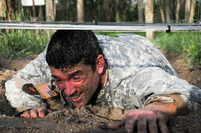 Staff Sgt. Nicholas Dombey, unit mobilization assistant with 205th Infantry Brigade, Camp Atterbury Joint Maneuver Training Center, drags his tired body through dirt and sand in the confidence course portion of zero day of an Air Assault.