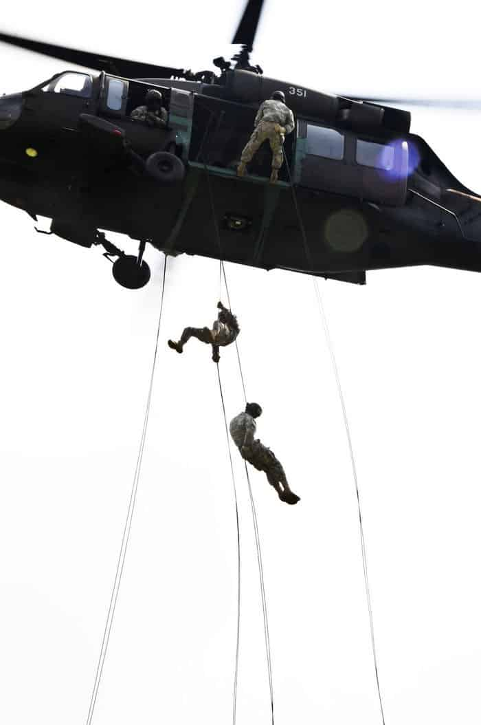 At the Air Assault Course, Camp Atterbury Joint Maneuver Training Center, students rappel 90 feet out of a UH 60 Blackhawk helicopter.