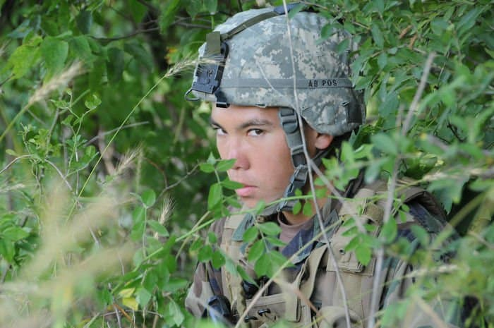 Sea Cadet Michael Morita, of San Diego, keeps a watchful eye over a secured landing zone from the cover of a tree line.