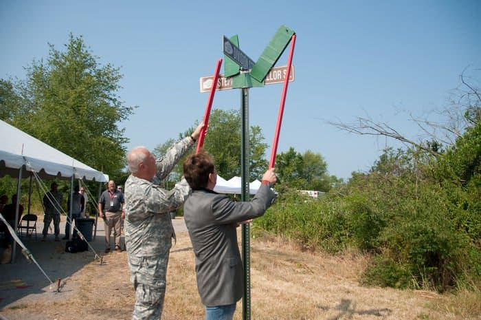 Maj. Gen. R. Martin Umbarger, Adjutant General Indiana National Guard, and Stephen Chancellor, CEO of American Patriot Group and chairman of AmeriQual Group, unveil the sign for a street named in Chancellors honor at a groundbreaking ceremony for the construction of new the Operational Readiness Training Complexes at Camp Atterbury Joint Maneuver Training Center, Ind.