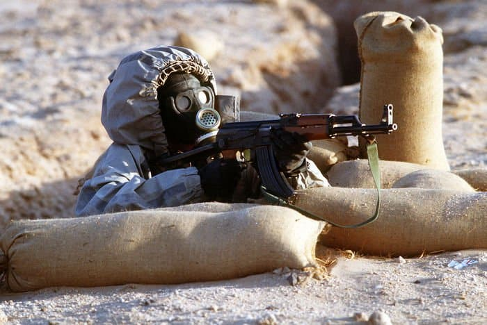 Syrian soldier wearing chemical warfare mask aims AK47.jpg