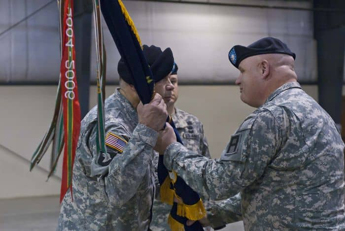 Lt. Col. Craig S. Wagoner, outgoing commander of the 1st Battalion, 335th Infantry Regiment, surrenders the regimental colors to Col. John F. Dunleavy, commander of the 205th Infantry Brigade, First Army Division East, at the 1 335th Change of Command Ceremony, Camp Atterbury Joint Maneuver Training Center, Ind.