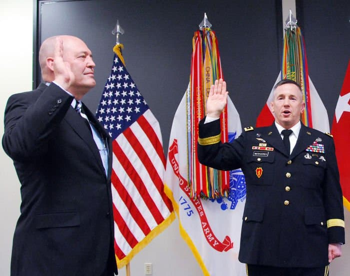 Retired Rear Adm. Sam Kupresin is sword in by First Army Commander Lt. Gen. Mick Benarek.