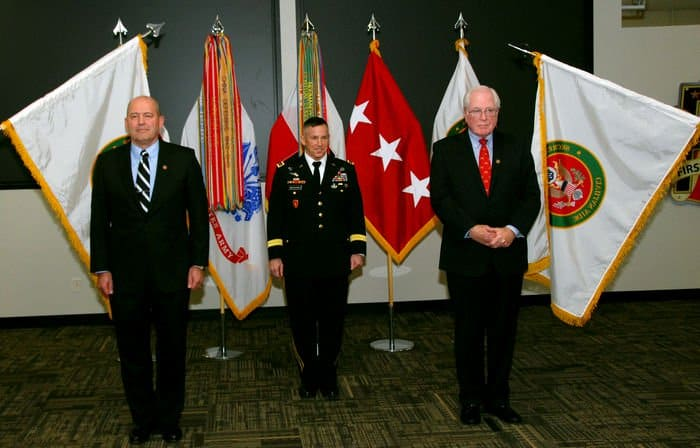 Retired Rear Adm. Sam Kupresin, First Army Commander Lt. Gen. Mick Benarek, and former University of Illinois professor Michael Ayers stand as the audience applauds during an investiture ceremony on Rock Island Arsenal.