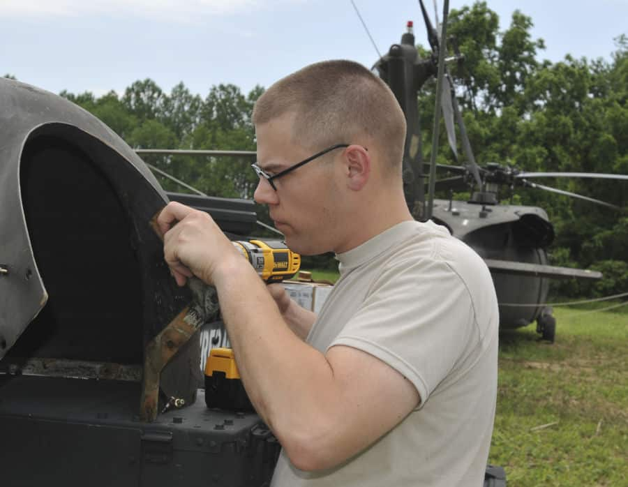 Pvt. Robert Dennison, Company D, 1st Battalion, 137th Aviation Regiment, Ohio National Guard, Columbus, Ohio, repairs a fastener on a UH 60 Black Hawk helicopter panel at Muscatatuck, near Butlerville, Ind.