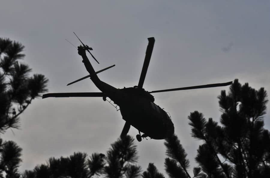A UH 60 Black Hawk helicopter of the 1st Battalion, 137th Aviation Regiment, Ohio National Guard, flies over the trees at Muscatatuck, near Butlerville, Ind.