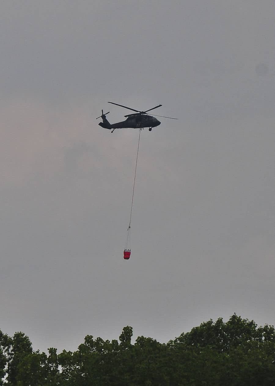 A UH 60 Black Hawk helicopter carries a fire suppression water bucket in annual training at Muscatatuck, near Butlerville Ind. The training focuses on tasks such as sling loading equipment, aerial firefighting and field maintenance of aircraft.