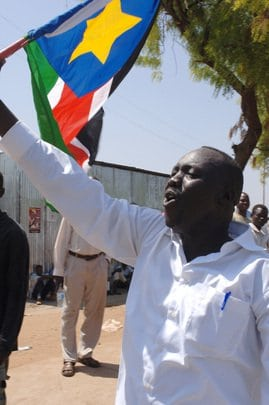 A young man, carrying a South Sudan flag, chants for independence, during the visit of Omar Hassan Ahmad AlBashir, President of Sudan, on the eve of the independence of South Sudan on 9 July 2011. UN Photo.