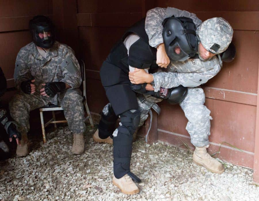 Sgt. 1st Class Josiah Elzy, trainer / mentor of the Combatives School trains a soldier in combat gear.