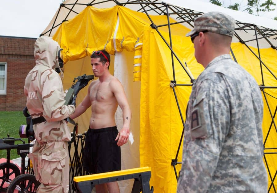 Sgt. 1st Class Dusty Beam, observer/controller/trainers of 157th Infantry Brigade, First Army Division East observes a Soldier of the 468th Engineer Detachment (Firefighters), out of Danvers, Mass., decontaminate a displaced civilian, at Muscatatuck Urban Training Center near Butlerville, Ind.