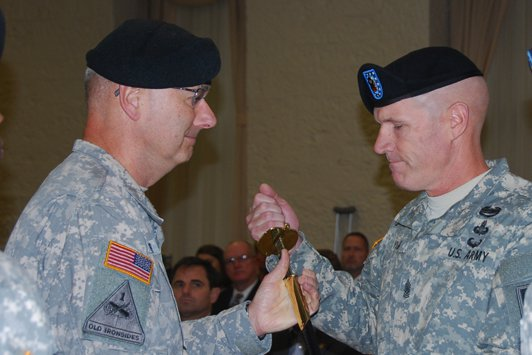 Command Sgt. Maj. Sam Young receives the sword from Lt. Gen. Michael Tucker, First Army commander, recognizing him as the new First Army senior enlisted leader in a change of responsibility ceremony at Rock Island Arsenal Heritage Hall.