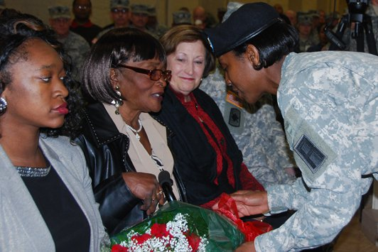 Sgt. 1st Class Leslie Ceasor presents a bouquet of red roses to Hattie Murray, mother of outgoing First Army Command Sgt. Maj. Jesse Andrews, at a Change of Responsibility ceremony Friday in Heritage Hall on Rock Island Arsenal. Andrews relinquished responsibility to Command Sgt. Maj. Sam Young.