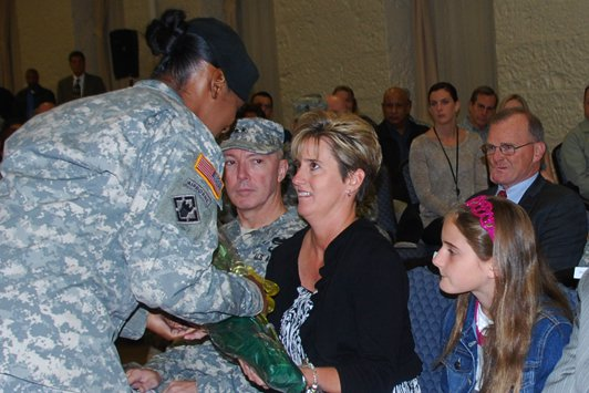 Staff Sgt. Tashanna Thomas presents a bouquet of yellow roses to Rhonda Young, wife of incoming First Army Command Sgt. Maj. Sam Young, at a Change of Responsibility ceremony in Heritage Hall on Rock Island Arsenal. Young took responsibility from outgoing Command Sgt. Maj. Jesse Andrews.
