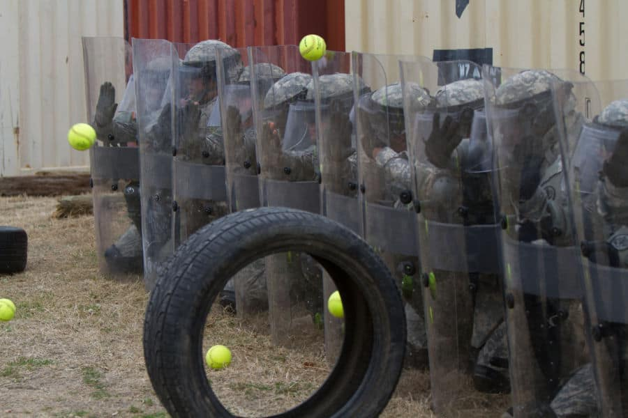 Soldiers hold a riot formation while being handling incoming practice projectiles.
