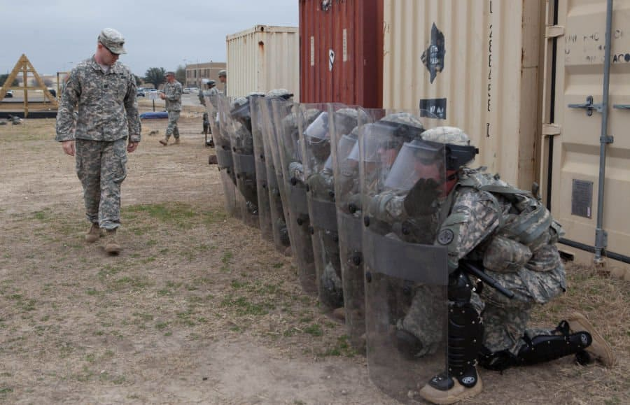 Soldiers prepare for nonlethal weapons training behind riot shields.