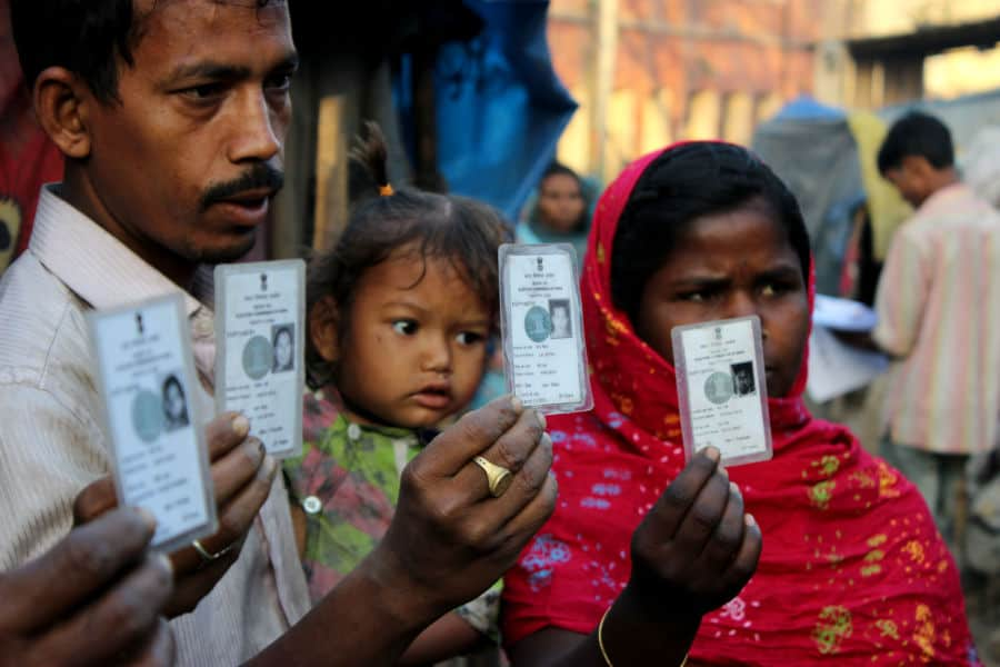 Elections in India, people displaying election cards before going to cast their vote. Photo Ahmad Mukhtiyar.