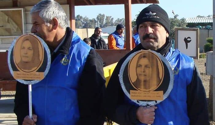 An Iranian Dissident in Camp Liberty holds a poster of Ms. Mahin Afzali, the 23rd victim of Iraq