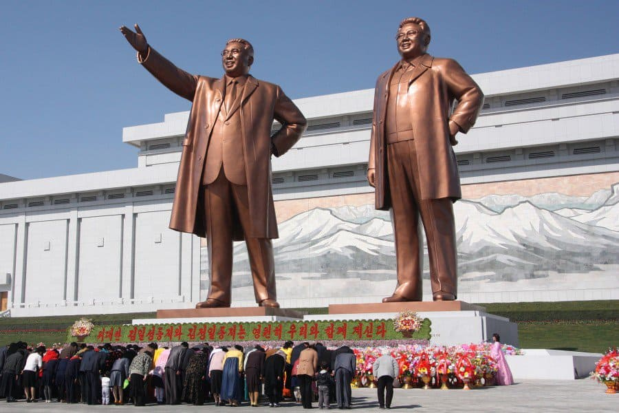 North Koreans bow in front of statues.
