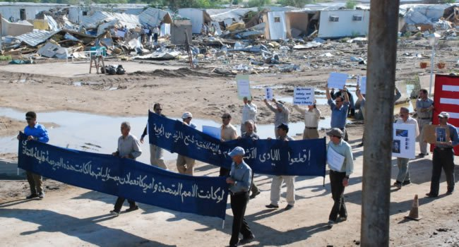 Camp Liberty residents walk their protest through the destroyed buildings after the missile attack.