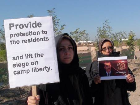 A woman holds a sign that says Provide protection to the residents and lift the siege on Camp Liberty.