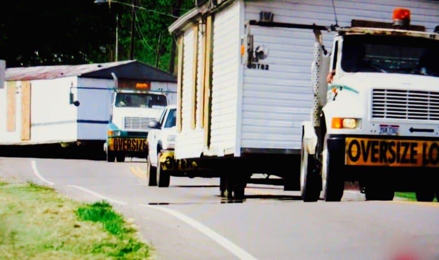 Rhoden case, trucks take homes on highway.