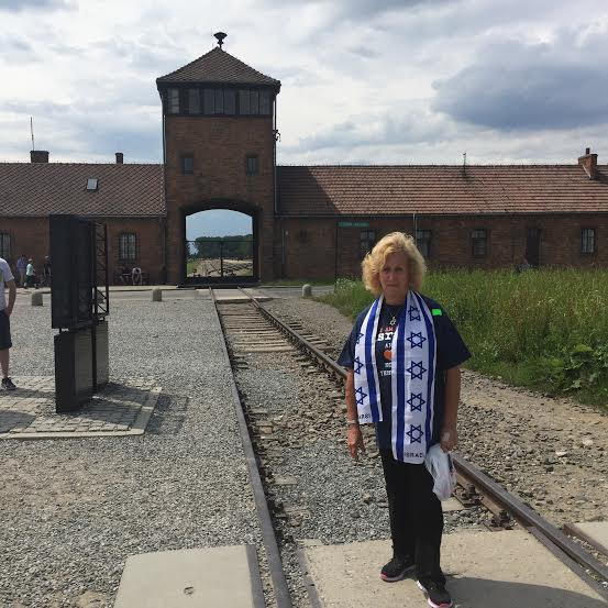 Auschwitz-Birkenau. The writer, standing near the infamous entrance of what was an entrance to hell.