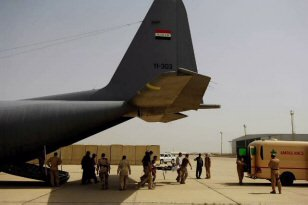 Members of the Iraqi Air Force unload a wounded Iraqi Army soldier from an Iraqi Air Force C-130 Hercules after a flight from Basra, Iraq to New Al Muthana Air Base in Baghdad Mar. 30. All processing, loading and transporting of the Iraqi troops was conducted by the Iraqi Air Force.