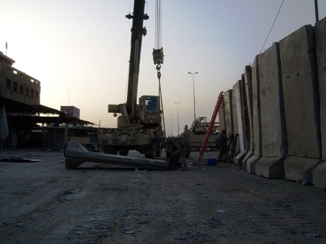 Soldiers rig a 14,000-pound T-wall barrier to a crane.