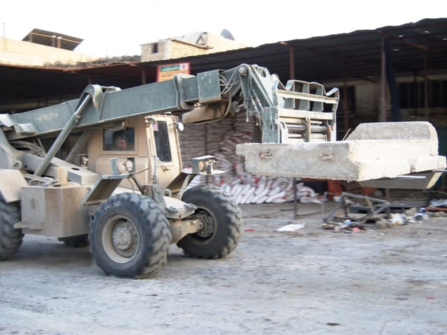 Spc. Bradley Convery, Heavy Equipment Operator moves a 14,000-pound T-wall barrier.
