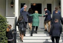 hillary clinton being helped up a short staircase.