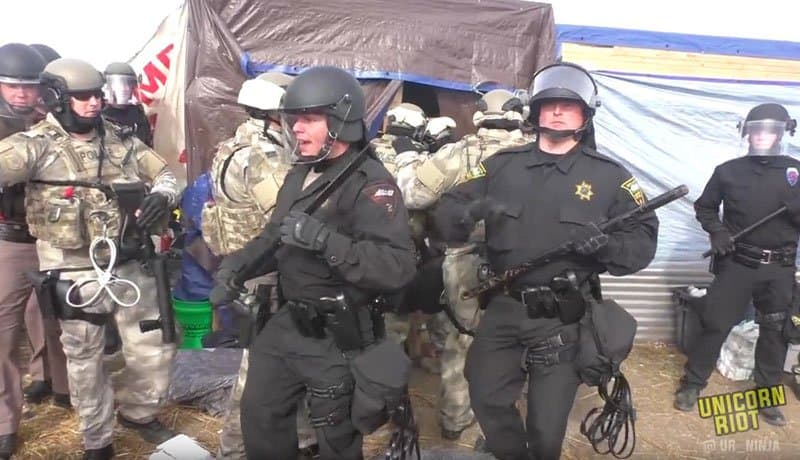 """doubletalk and heavily armed police attack unarmed sioux protestors. photo from @uc_ninja <a href=""""https://unicornriot.ninja"""">unicornriot.ninja</a>"""