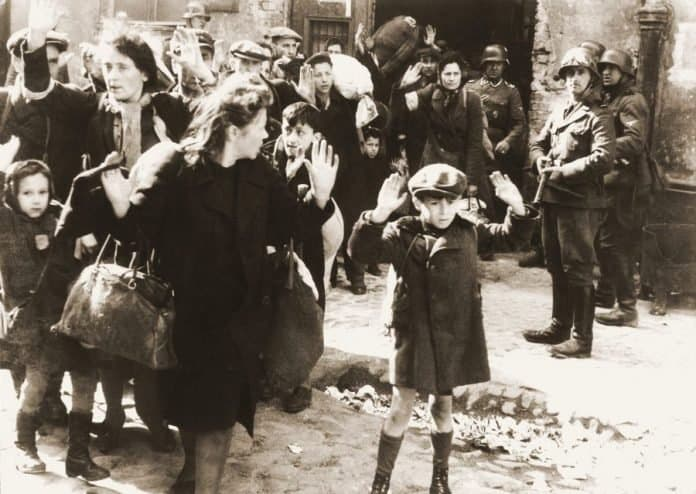 The infamous photo of a Jewish child at Warsaw Ghetto with Nazi guns threatening him
