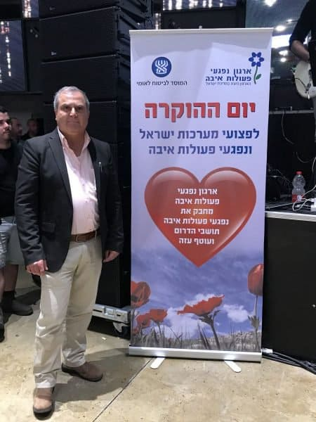 Victims of Hostilities and Terror Acts Organization - Abie Moses next to the event banner