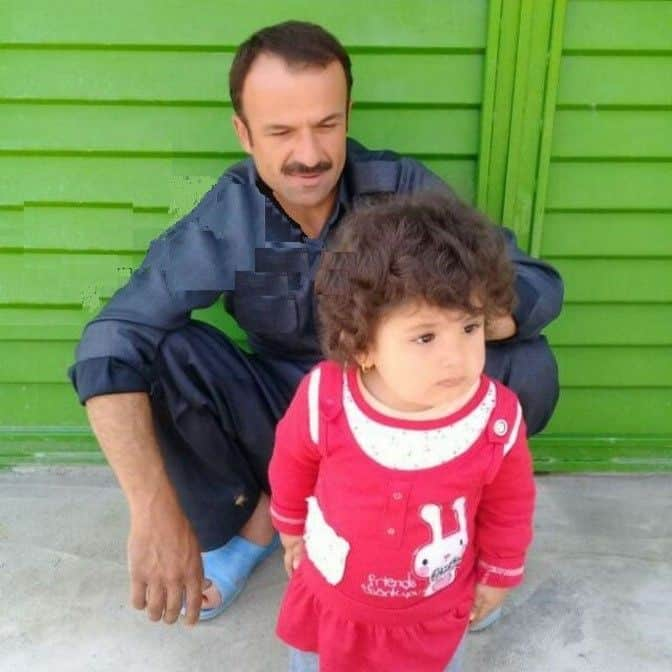 This porter (photographed sitting with his child) was shot last month by the regime's agents.