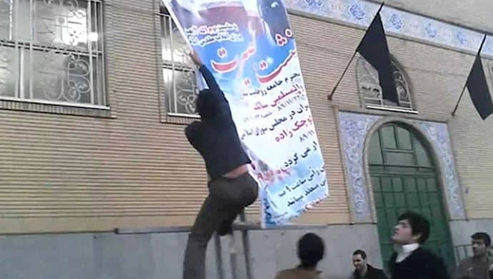 protestor erects banner - organized protests in Iran.
