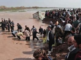 iran people cross flood