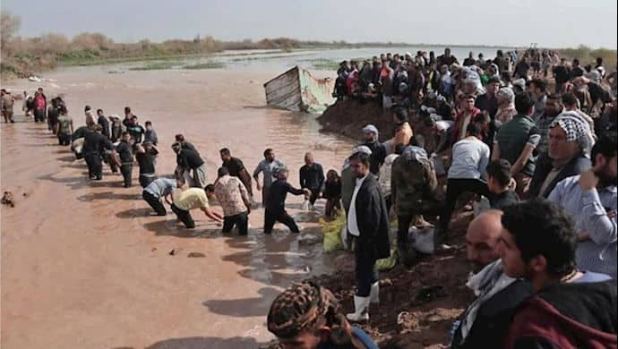 iran flood - people cross river