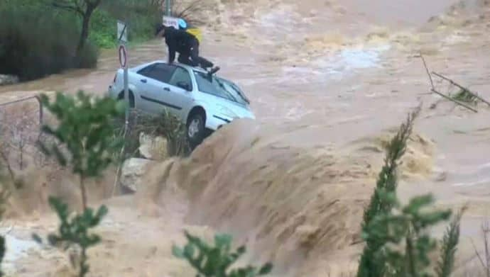 man trapped on car in flood