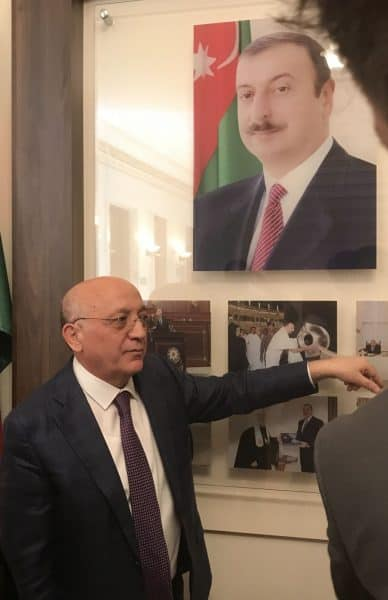 Committee on Religious Association-Mr. Gurbanli explains his committee's work - image of Ilham Aliyev, Azerbaijan's president in background