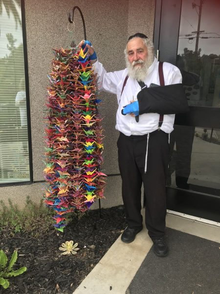 Rabbi Yisroel Goldstein in front of the synagogue-an anonymous prepared this colorful statue made of hundreds of paper birds of butterflies and dropped it there