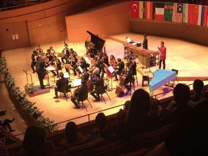 iPalpiti orchestra with Maestro conductor Eduard Schmieder-performing composer Franghiz Ali-Zadeh HARMONY composition-Azerbaijan flag in background