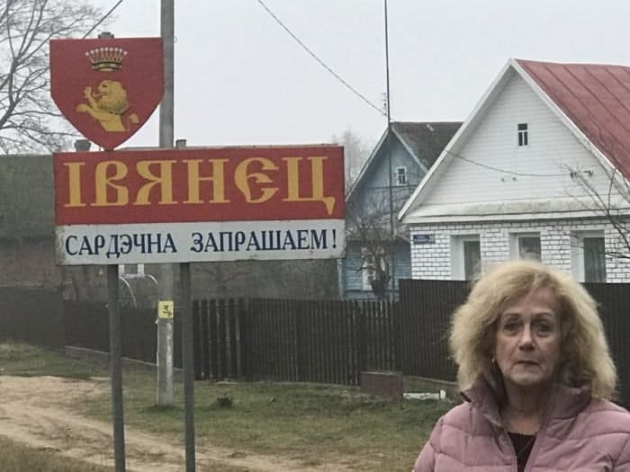 The writer, stressful, standing in front of the entrance sign to Ivainitz, Belarus, small town. - Photo credit Nurit Greenger