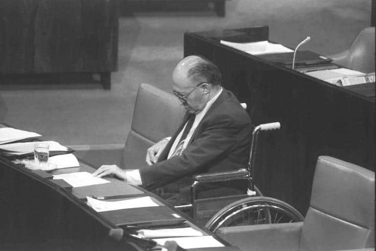 Prime Minister Menachem Begin sitting in a wheelchair   with a broken leg during the Knesset Golan Height annexation debate, December 14, 1981-Photographer Hanania Herman, GPO