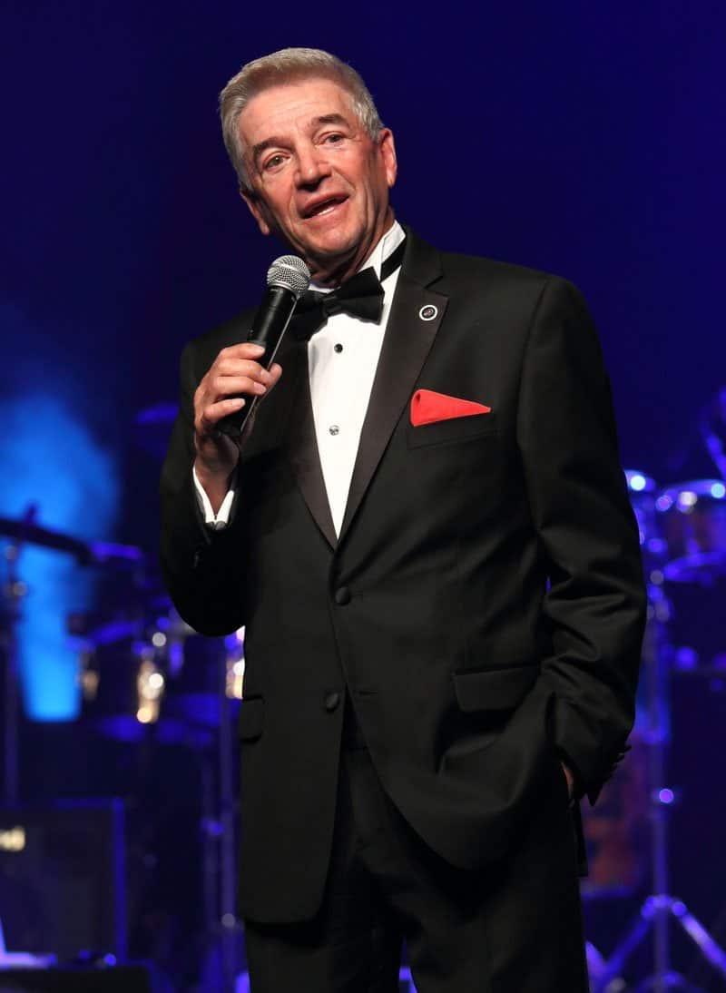 Tom Dreesen gravata preta em pé.  Foto c / o Tom Dreesen.