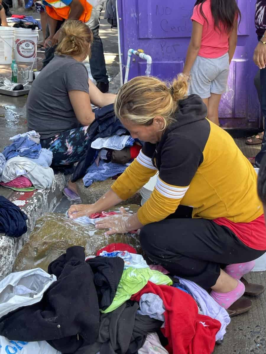 US-Mexico Border Migration Crisis, Laundry at the migrant tent city, soaping cloths on stone, rinsing with water carried in buckets - Photo credit Nurit Greenger