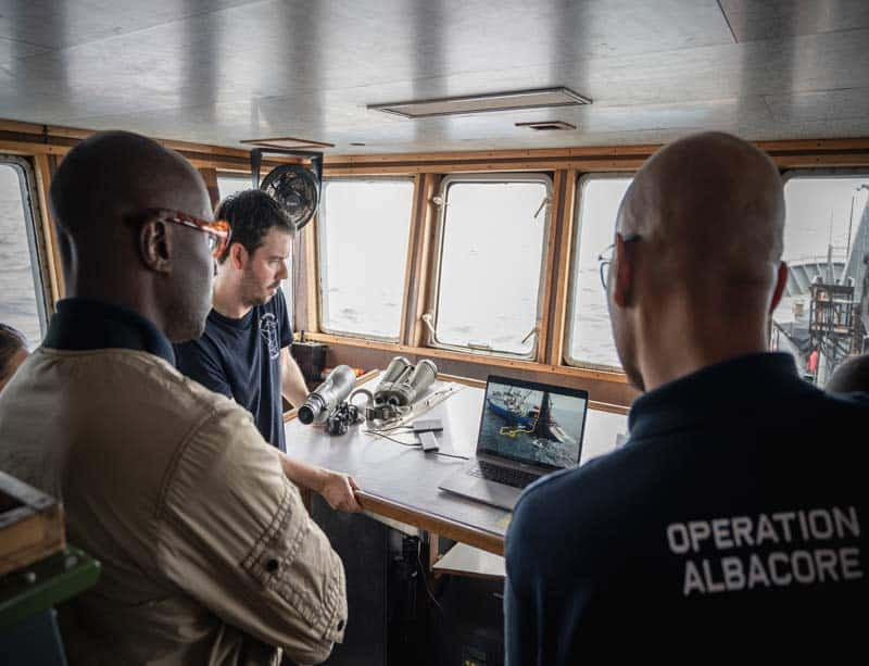 Peter and fishing minister of gabon watching bycatch on computer. Photo by Sea Shepherd Global.